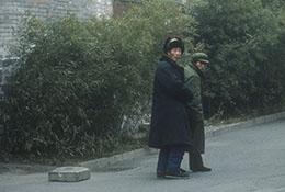 Two men walk in a lane near a Forbidden City tower, Beijing, China.