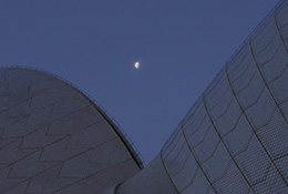 Opera house in Sydney, Australia, at twilight with moon.