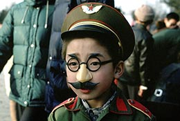 Child in Groucho Marx mustache and Chinese army costume, Beijing, China.
