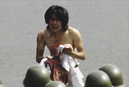 Injured protester faces off against police during Tiananmen crackdown.