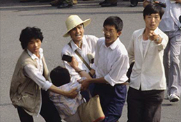 Protesters carry an injured person as they face off against police, Tiananmen crackdown, 1989.