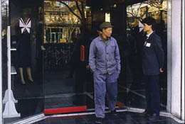 Man in worn Mao suit exits Pretty Fashions store in Beijing, China.