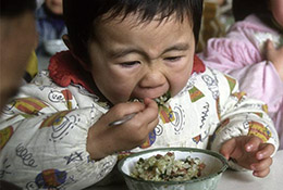 A child digs in to lunch at a kindergarten in Beijing, China.