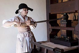 Colonial reenactor operates a printing press at Historic St. Mary's, Maryland.