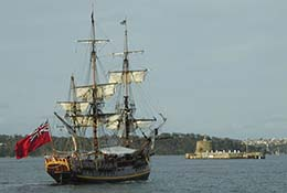 A replica of a historic ship sails past Fort Denison in Sydney Harbor, Australia.
