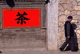 "Man walks past a sign that says ""tea"" at the Summer Palace, Beijing, China."