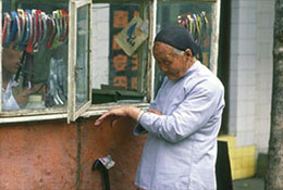 A woman with bound feet checks her watch, Beijing, China.