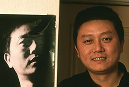 Chinese writer Wang Shuo with a poster advertising one of his books, Beijing, China.