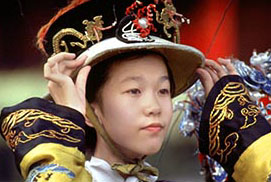 Chinese tourist poses in imperial garb at the Forbidden City, Beijing, China.