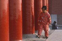 Young girl and red columns at the Forbidden City, Beijing, China.