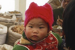Woman holds a baby at a spice market in Hunan, China.