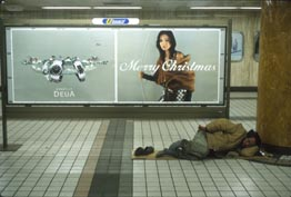 A Merry Christmas billboard and man sleeping in the subway, Tokyo, Japan.